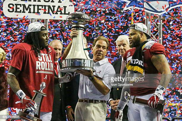 Alabama Crimson Tide head coach Nick Saban holds the trophy after the win over the Washington Huskies during the SemiFinal Peach Bowl between the...