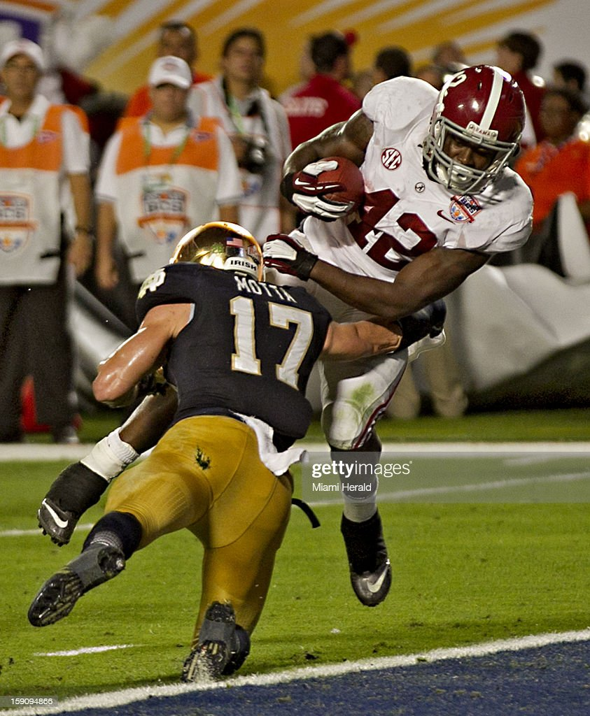 Alabama running back Eddie Lacey (42) scores a touchdown over Notre Dame safety Zeke Motta in the second quarter in the BCS National Championship game at Sun Life Stadium on Monday, January 7, 2013, in Miami Gardens, Florida.