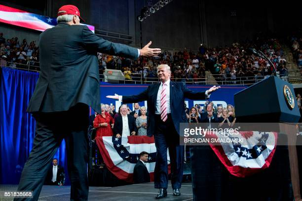 Alabama state Republican Senator Luther Strange walks to embrace US President Donald Trump during the senator's rally at the Von Braun Civic Center...