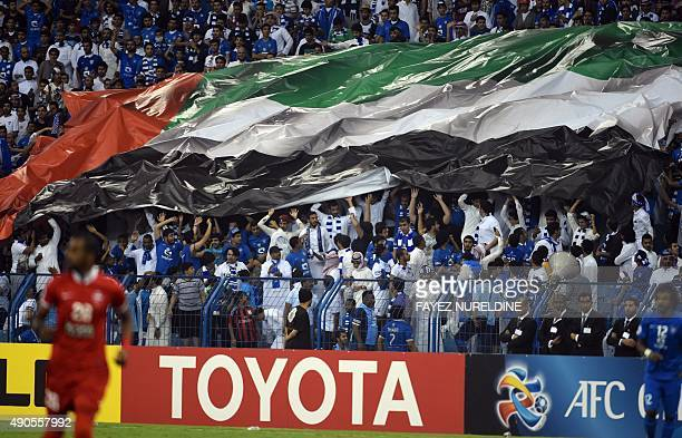 AlAhli fans hold up a large United Arab Emirates flag during the AFC Champions League semifinal football match between AlHilal and AlAhli on...