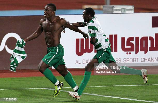 AlAhli's Ivorian forward Olivier Tia celebrates with his teammate Adel Ahmed after scoring a goal against Umm Salal during their Qatar Stars League...