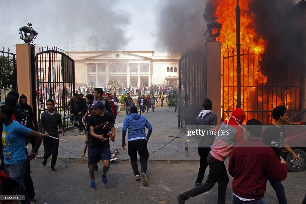 Al-Ahly club supporters run away from smoke and flames rising from the police officers' club in Cairo on March 9, 2013, after several buildings in the complex were set on fire. According to a senior security official, hardcore Al-Ahly football fans, known as the Ultras, stormed the complex and set fire to the buildings after an Egyptian court upheld death sentences for 21 defendants over a deadly football riot in Port Said last year. AFP PHOTO / STR