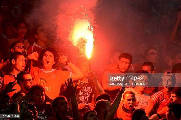 AlAhly fans cheer as one of them carries a flare during their CAF Champions League group A stage football match between Egypt's AlAhly and Morocco's...
