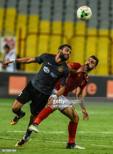 AlAhly's Abdallah AlSaid vies for the ball with Esperance of Tunis' Dhaouadi during the CAF Champions League quarterfinal firstleg football match...