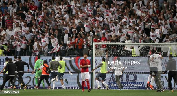 AlAhly's Moamen Zakaria walks away as Zamalek's players rush the field to celebrate their victory during the Egyptian Super Cup football match...