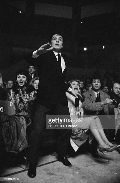 Alain Delon At A Boxing Match Alain DELON assiste à un match de boxe attitude de l'acteur debout un bras tendu en avant une femme assise à ses côtés...