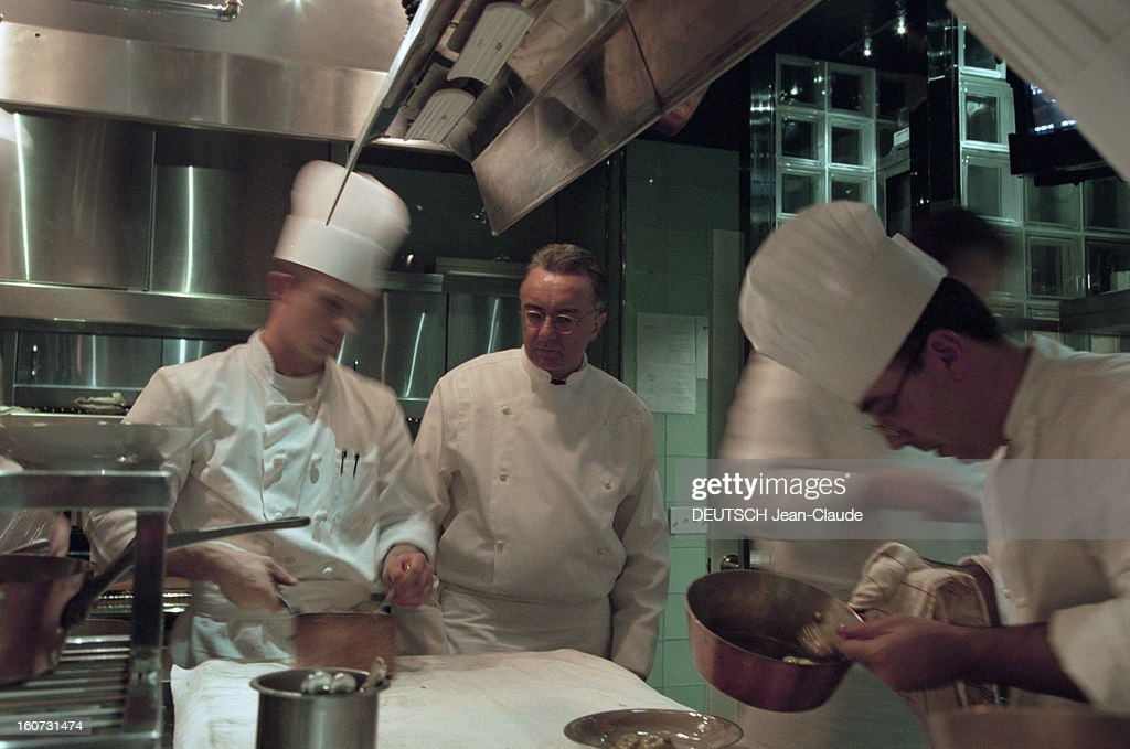 Alain Ducasse At His Restaurant 'the Essex House' In New York. Aux États-Unis, à New York, le 19 septembre 2000. Le chef cuisinier français Alain DUCASSE dans son restaurant ' The Essex House' ouvert en juin 2000 dans le centre de Manhattan.Dans sa cuisine, Alain DUCASSE en blouse blanche regardant un de ses employés tenir une casserole devant un autre employé penché sur une casserole. .