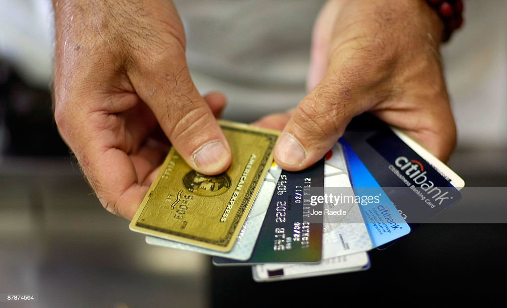 Alain Filiz shows off some of his credit cards as he pays for items at Lorenzo's Italian Market on May 20, 2009 in Miami, Florida. Members of Congress today passed a bill placing new restrictions on companies that issues credit. The vote follows the Senate passage of the bill, which now heads for President Obama's promised signature. The bill will curb sudden interest rate increases and hidden fees, requiring card companies to tell customers of rate increases 45 days in advance. It will also make it harder for people aged below 21 to be issued credit cards.