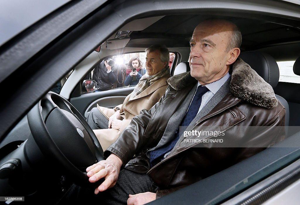 Alain Juppe (R), Mayor of Bordeaux, drives on February 26, 2013 an electric Bluecar next to French businessman Vincent Bollore during the car's presentation at the Bordeaux Town Hall.