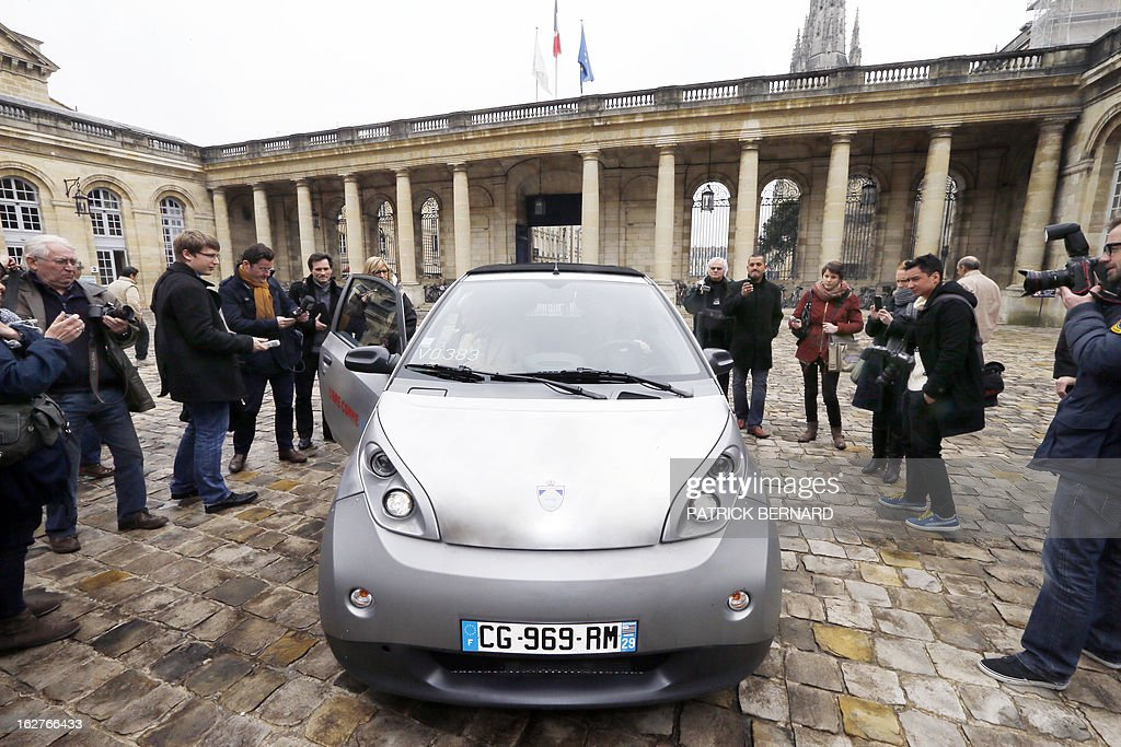Alain Juppe (R), Mayor of Bordeaux, drives on February 26, 2013 an electric Bluecar next to French businessman Vincent Bollore during the car's presentation at the Bordeaux Town Hall. AFP PHOTO / PHOTO PATRICK BERNARD
