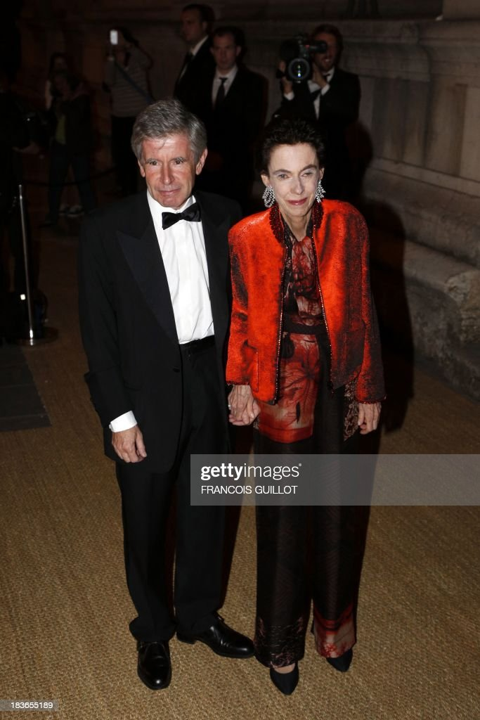 Alain Minc, writer and head of a French consultancy agency poses with his wife as he arrives at Paris Beaux Arts school to take part in a dinner organized by US fashion designer Ralph Lauren to celebrate his sponsorship with the school, on October 8, 2013 in Paris.