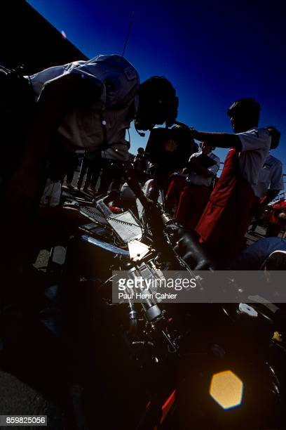 Alain Prost McLarenHonda MP4/4 Grand Prix of Portugal Autodromo do Estoril September 25 1988 A Honda mechanic inspecting the Honda RA168E 15 V6 turbo...