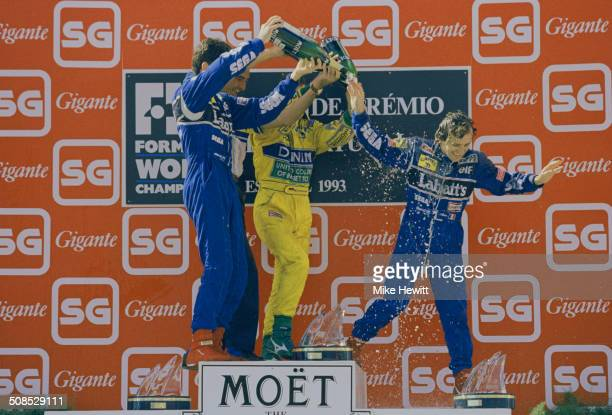 Alain Prost of France is showered in champagne by race winner Michael Schumacher and third placed team mate Damon Hill after the Portuguese Grand...