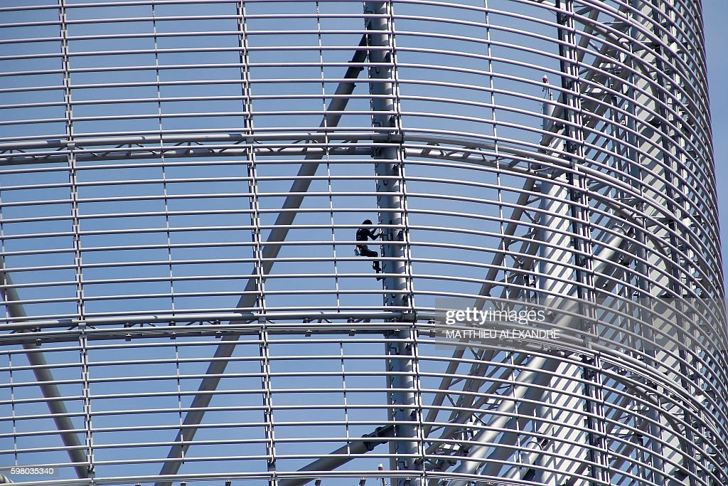 Alain Robert a French urban climber aka Spiderman climbs up a building of La Defense business area on August 31 2016 in Courbevoie near Paris / AFP /...