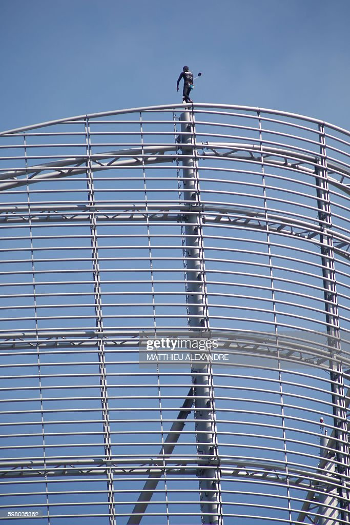 Alain Robert a French urban climber aka Spiderman takes a selfie as he stands on top of a building of La Defense business area on August 31 2016 in...