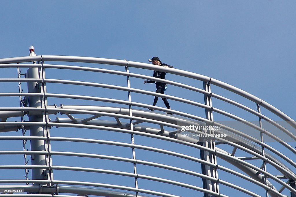 Alain Robert a French urban climber aka Spiderman walks on top of a building of La Defense business area on August 31 2016 in Courbevoie near Paris /...