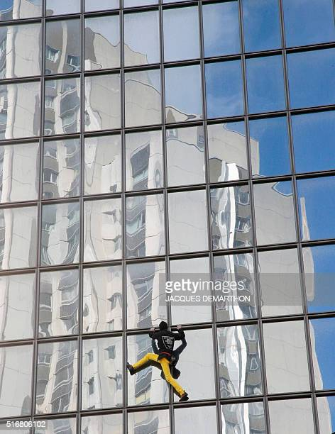 Alain Robert the French urban climber dubbed Spiderman climbs a building hosting the headquarters of French oil giant Total at La Defense business...