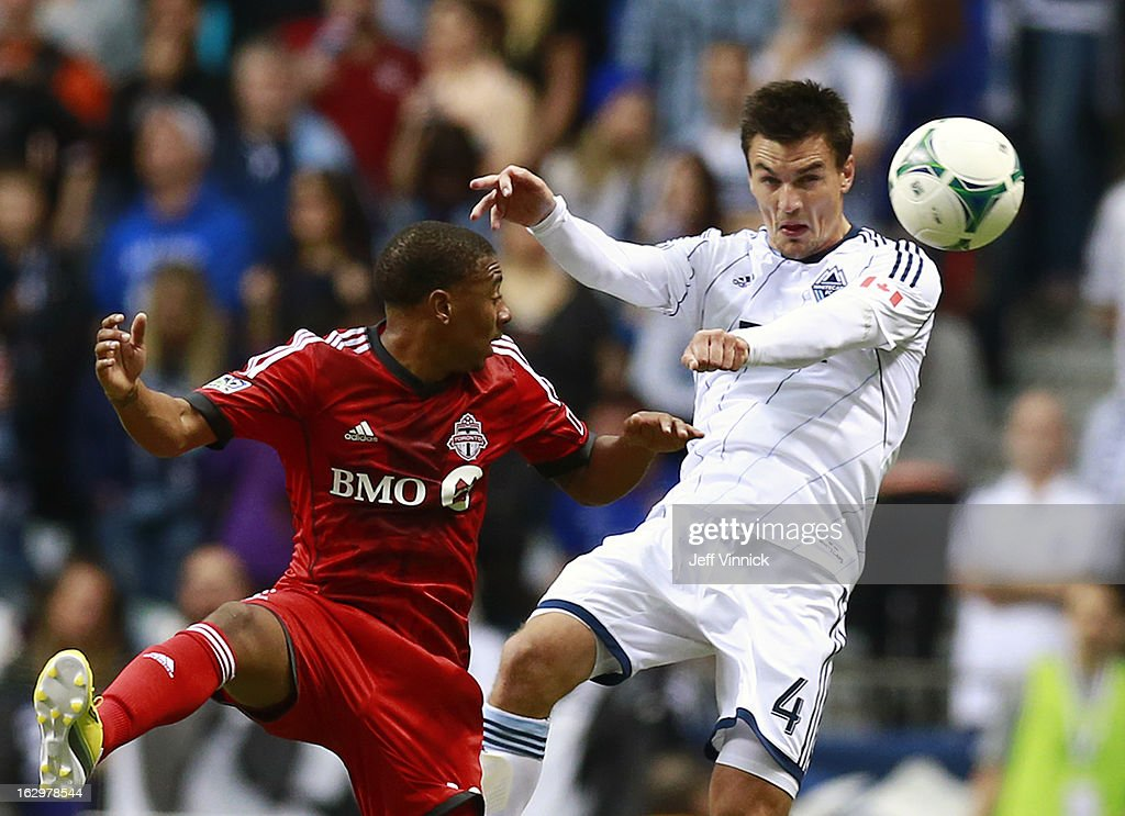 Alain Rochet #4 of the Vancouver Whitecaps FC heads the ball away from Reggie Lambe #19 of the Toronto FC during their MLS game at BC Place March 2, 2013 in Vancouver, British Columbia, Canada.