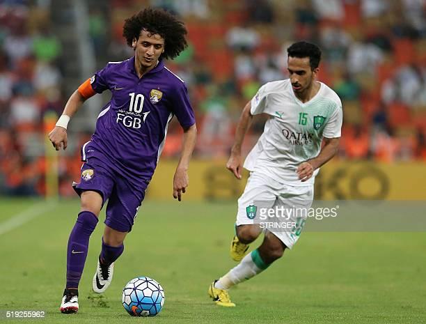 AlAin's Omar Abdulrahman dribbles past AlAhli's Saleh AlAjman during their AFC Champions League football match at King Abdullah Sports City in Jeddah...