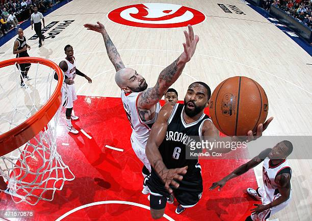 Alan Anderson of the Brooklyn Nets drives against Pero Antic and Paul Millsap of the Atlanta Hawks during Game Five of the Eastern Conference...