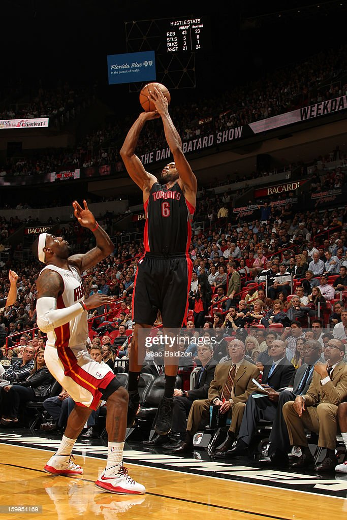 Alan Anderson #6 of the Toronto Raptors shoots a three pointer against LeBron James #6 of the Miami Heat on January 23, 2013 at American Airlines Arena in Miami, Florida.