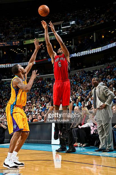 Alan Anderson of the Toronto Raptors shoots a threepointer as head coach Dwane Casey looks on against Dominic McGuire of the New Orleans Hornets on...