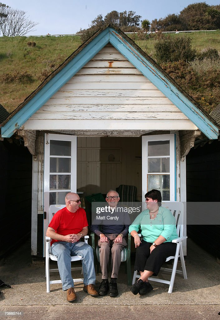 Alan Ball and Heather Ball chat with Roy Johnson (C) in a beach hut as he enjoys the hot weather on the sea front on April 14, 2007 in Bournemouth, England. The unseasonably warm weather has heralded the start to what forecasters predict will be a record breaking summer.
