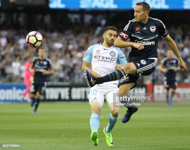 Alan Baro of the Victory clears the ball away from Anthony Caceres of Melbourne City during the round 18 ALeague match between Melbourne Victory and...