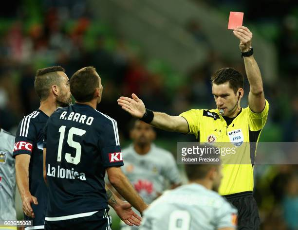 Alan Baro of the Victory receives a red card after applying a tackle on Kosta Barbarouses of the Phoenix during the round 25 ALeague match between...