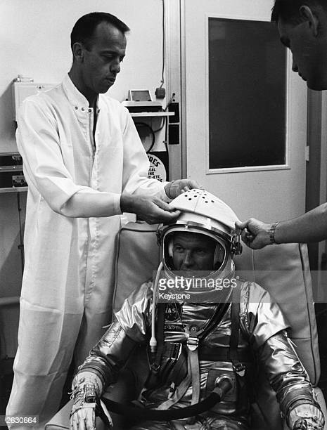 Alan Bartlett Shepard the American astronaut and backup to Cooper and Al Rochford is pictured being fitted with the protective covering on the visor...