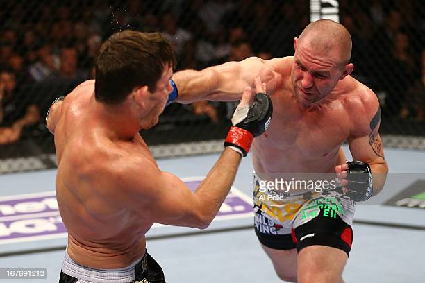 Alan Belcher punches Michael Bisping of England in thier middleweight bout during the UFC 159 event at the Prudential Center on April 27 2013 in...