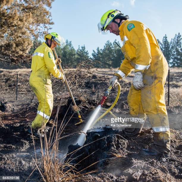 Alan Butterick and Barrie Begg of the Lauriston Rural Fire Force dig out and dampen down hotspots on February 20 2017 in Christchurch New Zealand...