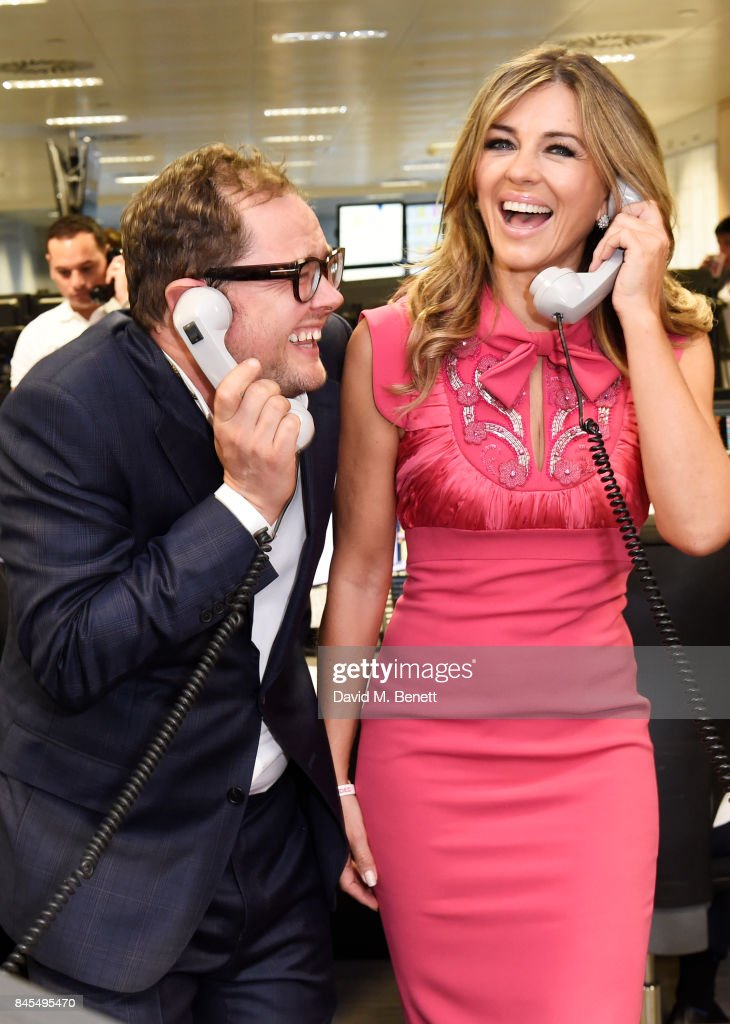 Alan Carr (L) and Elizabeth Hurley, representing Walking With The Wounded/Wounded Veterans Fund, make a trade at BGC Charity Day on September 11, 2017 in London, United Kingdom.