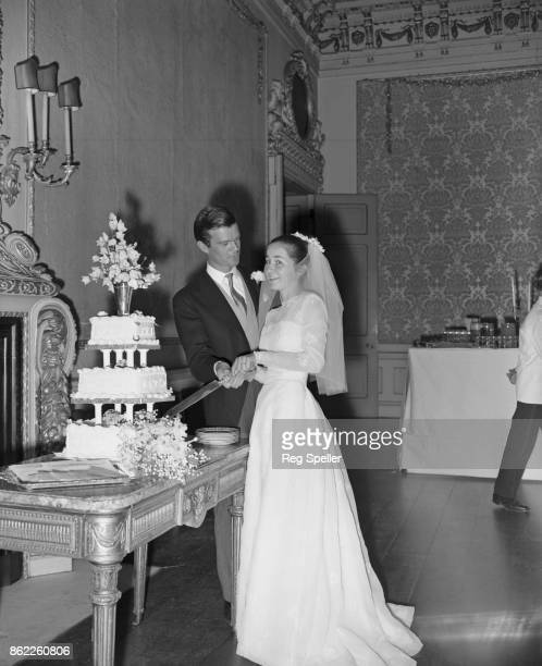 Alan Clark the son of Arts Council chairman Kenneth Clark cuts the cake with his new wife 16yearold Jane Beuttler during their wedding reception at...