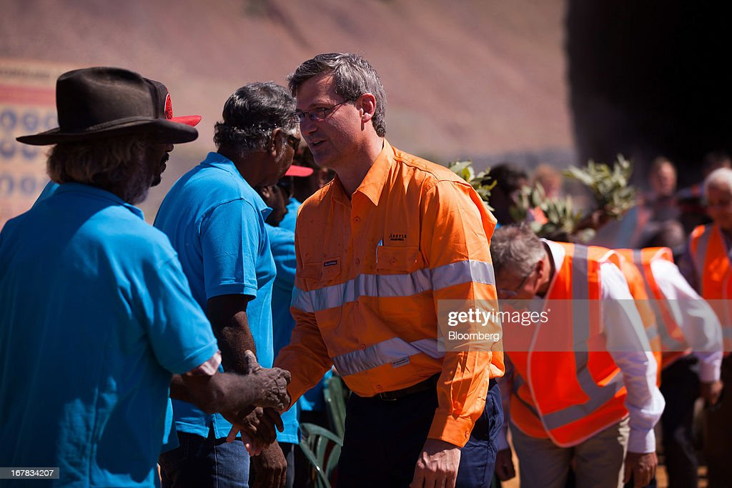 Alan Davies, chief executive officer of diamonds and minerals at Rio Tinto Group, right, shakes hands with representatives from the Mirriuwung and Gidja people, the traditional owners of the land, during the opening ceremony of the company's underground expansion of the Argyle diamond mine in Kimberley, Australia, on Tuesday, April 30, 2013. Production at Argyle, which supplies more than 90 percent of the world's pink diamonds, will rise to 20 million carats annually as production moves underground, while costs will fall. Photographer: Ian Waldie/Bloomberg via Getty Images