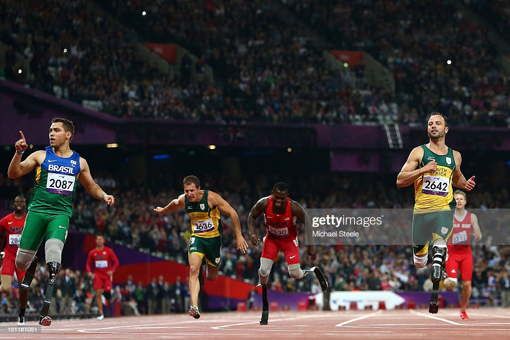 Alan Fonteles Cardoso Oliveira of Brazil crosses the line ahead of Oscar Pistorius of South Africa to win gold in the Men's 200m T44 Final on day 4...