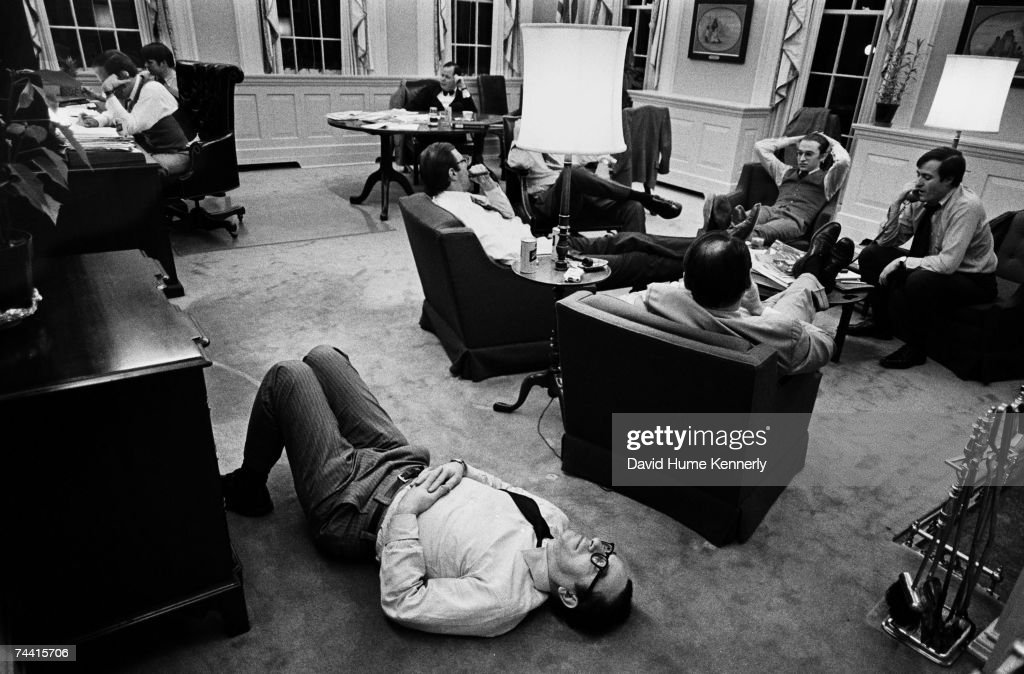 Alan Greenspan lays on the floor because of a bad back in Chief of Staff Dick Cheney's office Cheney on phone in background February 24 1976 in...