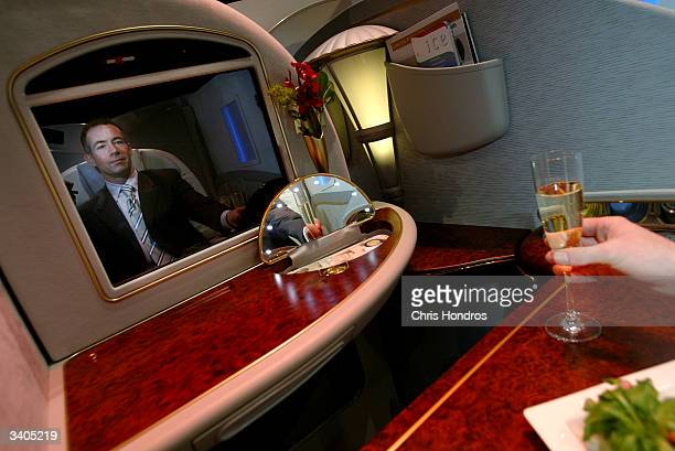 Alan Griffith of Emirates Airlines reaches for a glass of champagne in a display of a new first class individual cabin April 16 2004 at the Grand...