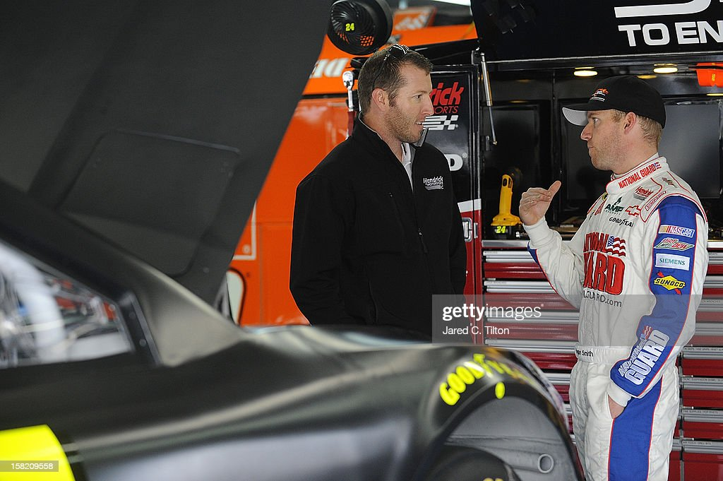 Alan Gustafson, crew chief of the #24 Drive To End Hunger Chevrolet, and Regan Smith, driver of the Hendrick Motorsports Chevrolet, speak in the garage area during testing at Charlotte Motor Speedway on December 11, 2012 in Concord, North Carolina.
