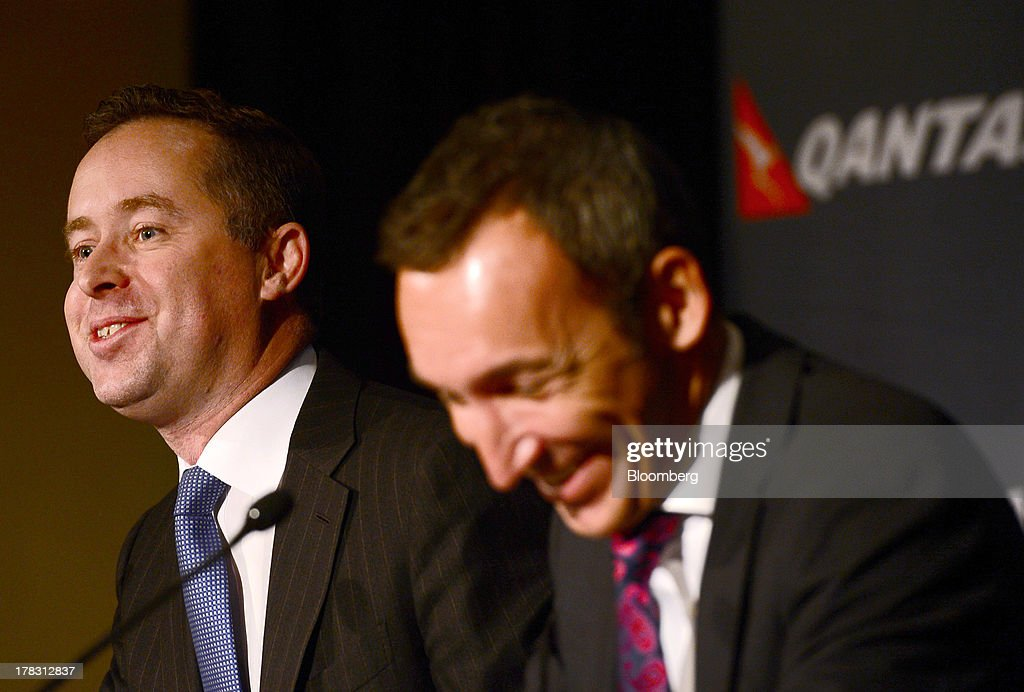 Alan Joyce, chief executive officer of Qantas Airways Ltd., left, speaks as Gareth Evans, chief financial officer, reacts during a news conference in Sydney, Australia, on Thursday, Aug. 29, 2013. Qantas, Australia's largest carrier, doubled its profits and beat analyst estimates as a tie-up with Emirates helped rein in long-haul losses. Its shares rose the most in a year. Photographer: Jeremy Piper/Bloomberg via Getty Images