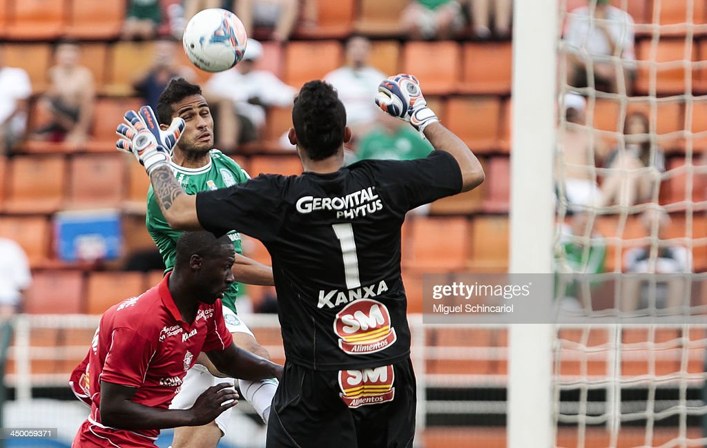 Alan Kardec (C) of Palmeiras fights for the ball with Rodrigo Souza (L) and goalkeeper Douglas of Boa Esporte during the match between Palmeiras and Boa Esporte for the Brazilian Championship Series B 2013 at Pacaembu Stadium on November 16, 2013 in Sao Paulo, Brazil.