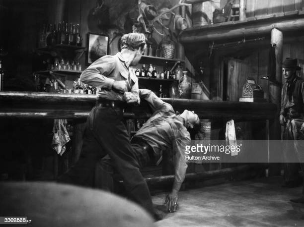 Alan Ladd lays Ben Johnson out cold in a bar room scene from the film 'Shane' directed by George Stevens for Paramount