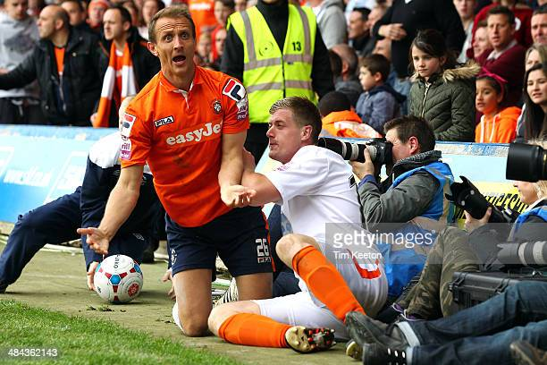 Alan Massey of Braintree Town and Paul Benson of Luton Town fall into some photographers as they tussle for the ball during the Skrill Conference...
