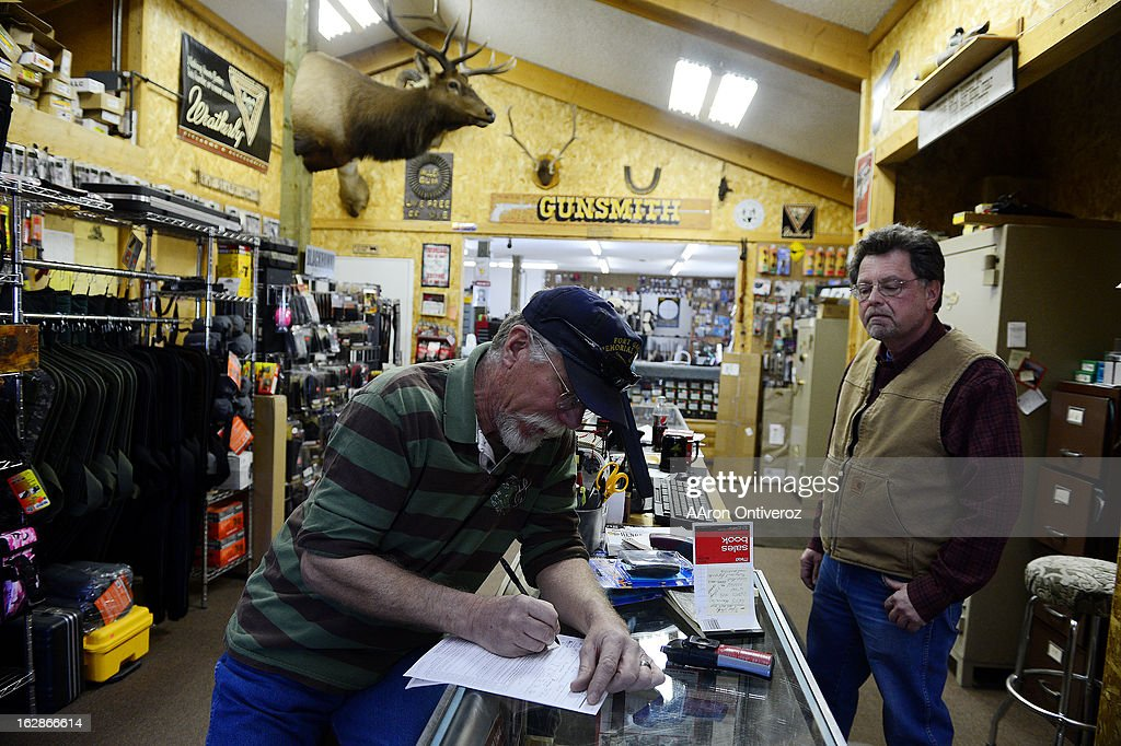 Alan McFadden fills out a background check as Valley Guns owner Carlton Thomas looks on. Thomas, who knows McFadden well, said that even if his own brother came in, he'd have to fill out the check. Gun owners in southern Colorado largely agree that responsible ownership begins at home.