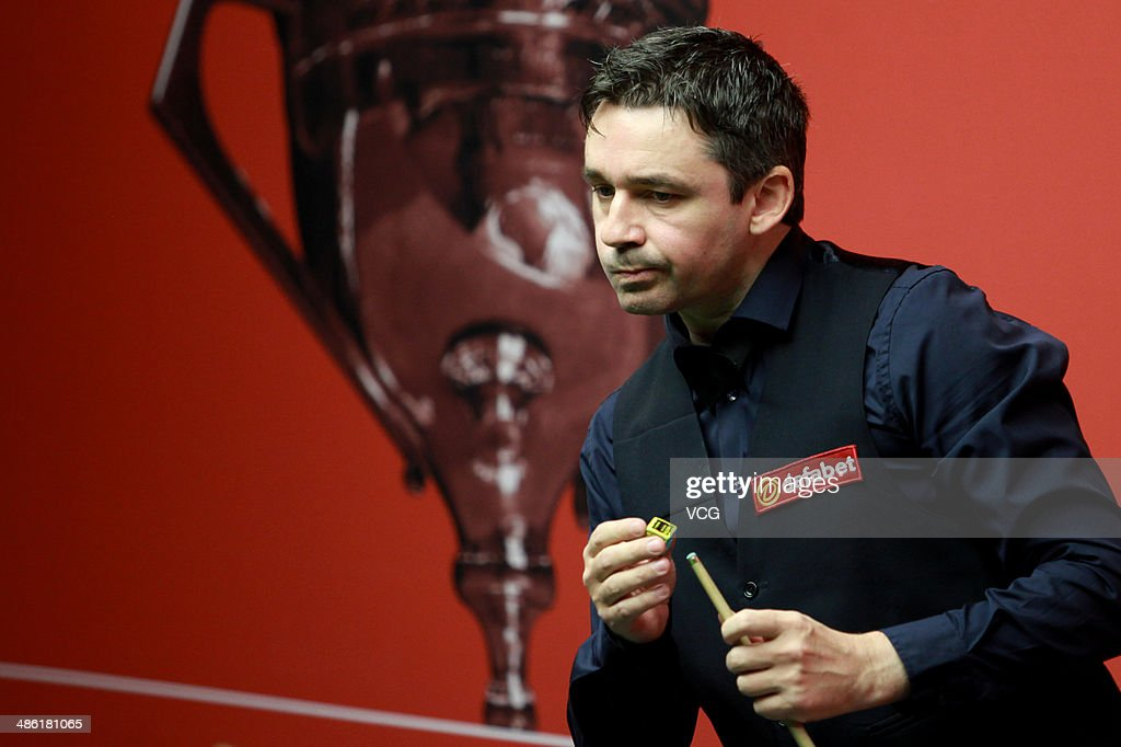 Alan McManus of Scotland chalks his cue against John Higgins of Scotland during day four of the The Dafabet World Snooker Championship at Crucible Theatre on April 22, 2014 in Sheffield, England.