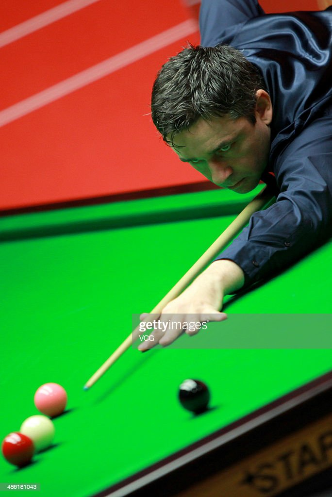 Alan McManus of Scotland plays a shoot against John Higgins of Scotland during day four of the The Dafabet World Snooker Championship at Crucible Theatre on April 22, 2014 in Sheffield, England.