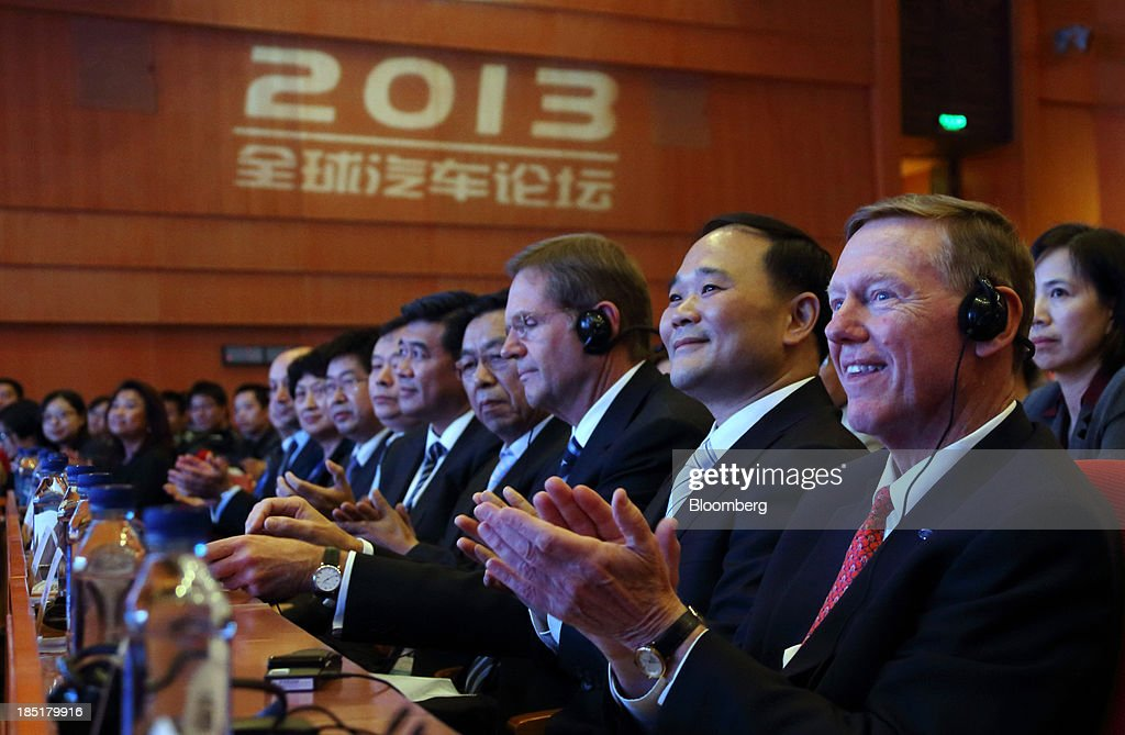 Alan Mulally, president and chief executive officer of Ford Motor Co., right, and Li Shufu, chairman of Geely Automobile Holdings Ltd., second from right, applaud as they attend a session at the Global Automotive Forum in Wuhan, China, on Friday, Oct. 18, 2013. The forum concludes today. Photographer: Tomohiro Ohsumi/Bloomberg via Getty Images