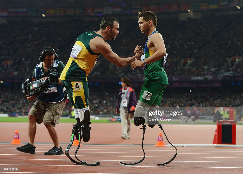 Alan Fonteles Cardoso Oliveira of Brazil is congratulated by Oscar Pistorius of South Africa after winning gold in the Men's 200m T44 Final on day 4...