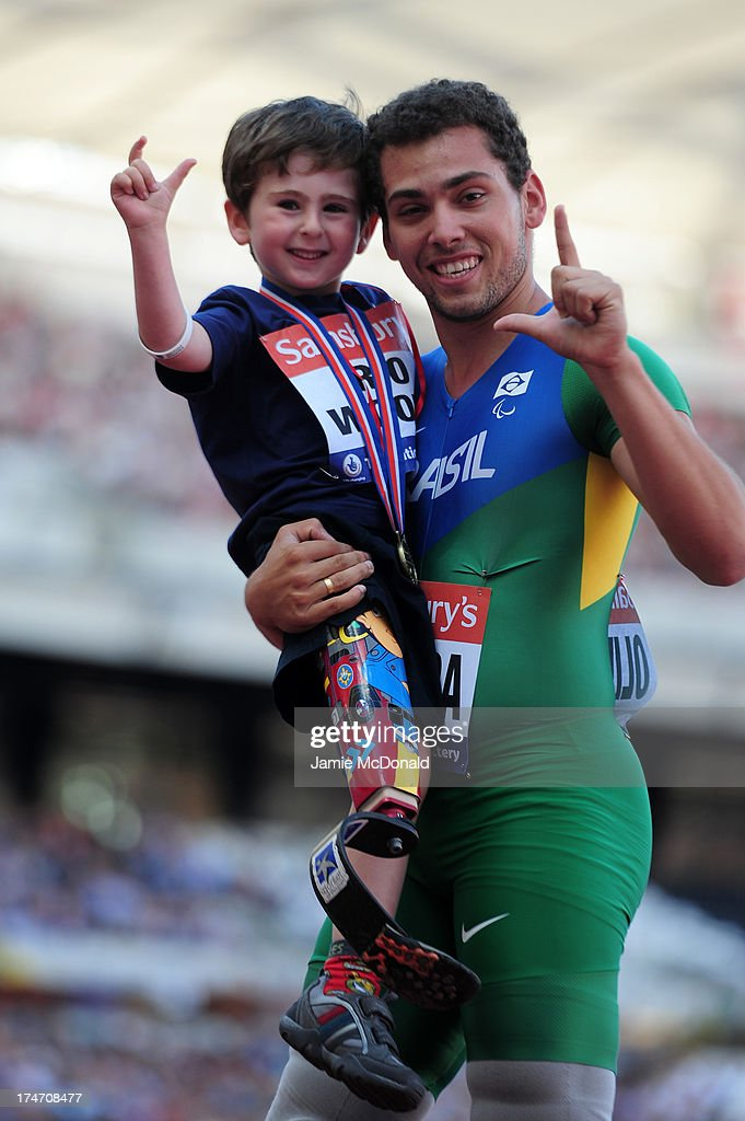 Alan Oliveira of Brazil poses with 5 year old Rio Woolf after winning the Men's T43/44 100mduring day three of the Sainsbury's Anniversary Games IAAF...