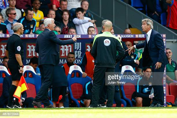 Alan Pardew manager of Crystal Palace exchanges words with Manuel Pellegrini manager of Manchester City during the Barclays Premier League match...